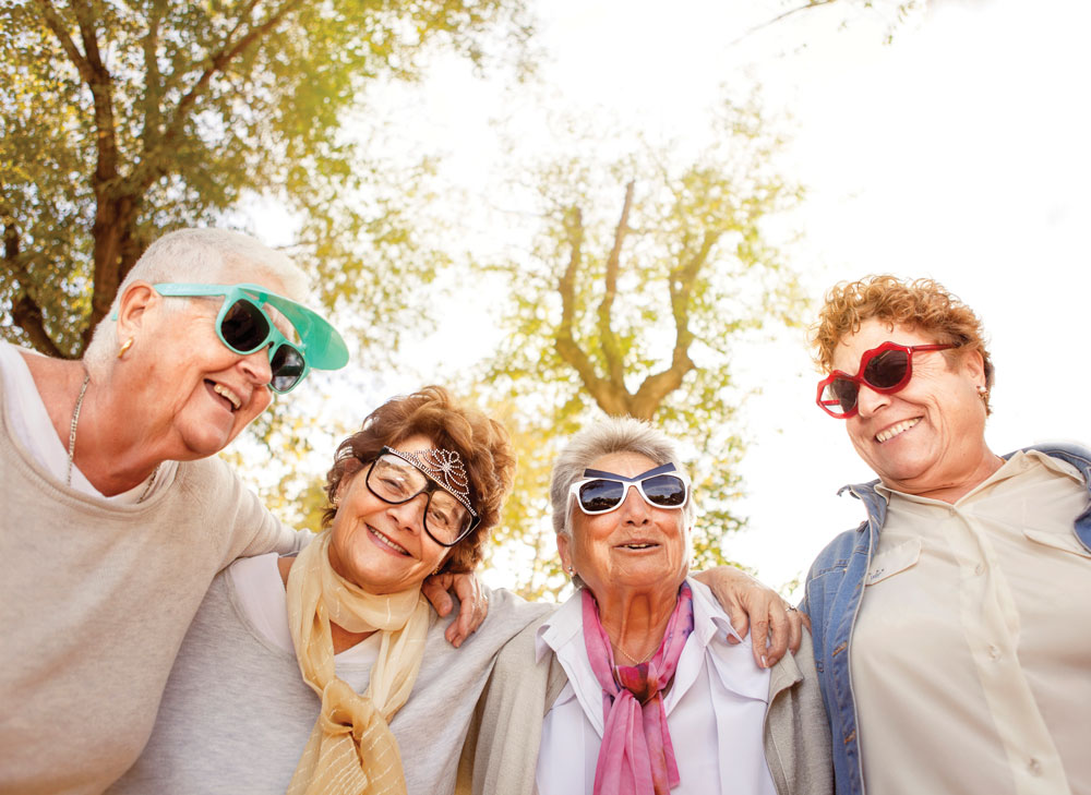 Four older women pose close together in funny sunglasses outdoors