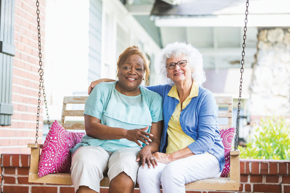Two Charter Senior Living of Panama City Beach female residents sit closely together and smile on outdoor swing