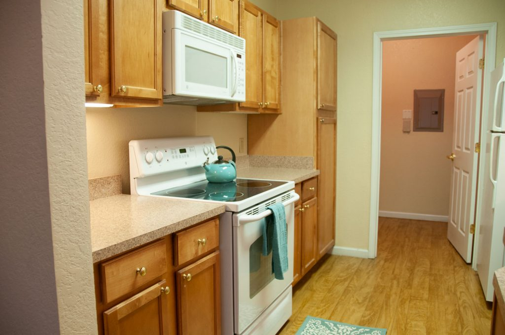 Kitchen with stove, countertops, cabinets, microwave, refrigerator, and hardwood floors