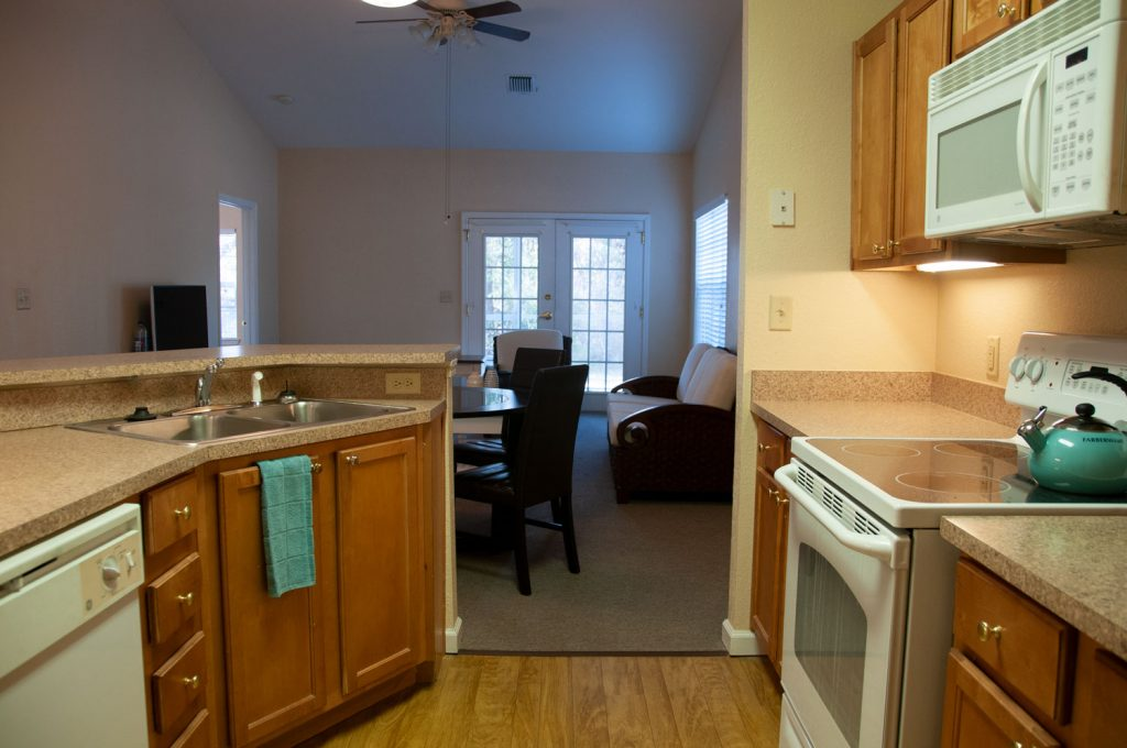 Kitchen with stove, microwave, counters, island, dishwasher, sink, and view of living/dining areas