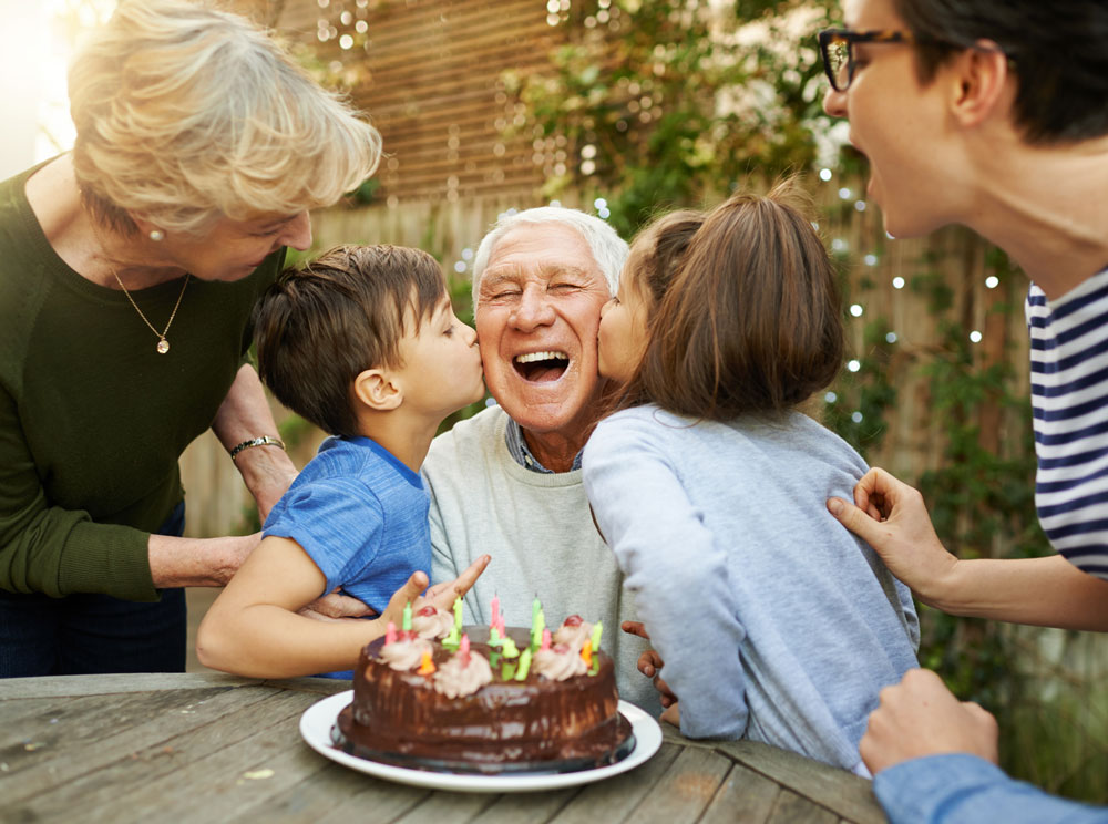 Senior aged male celebrates birthday outdoors with his family, kisses on his cheek from young children, and a birthday cake