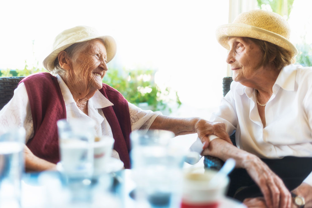 Two female senior living residents in hats sit at outdoor table and smile at each other