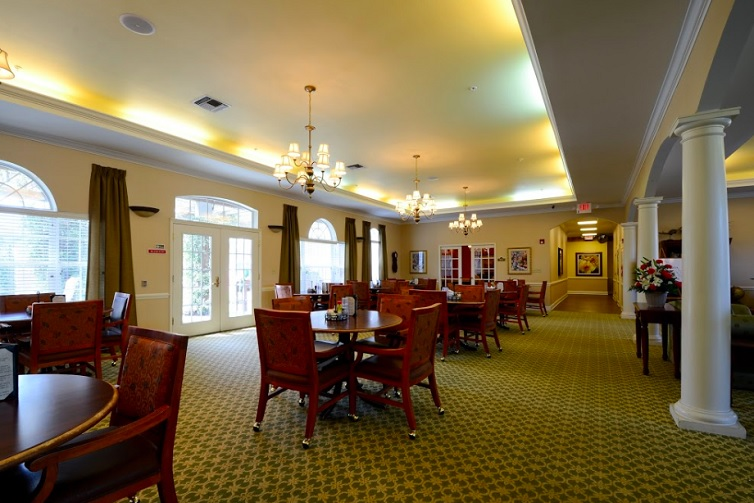Large open dining room with many tables and chairs and chandeliers hanging overhead